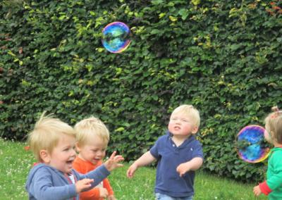 Nikibel kinderopvang spelen in de tuin zeepbellen
